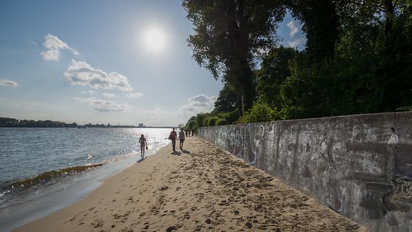 Elbstrand mit spazieren gehenden Menschen Hamburg bei Sonne