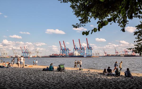 Elbstrand mit Menschen Hafen am Tag bei Hamburg