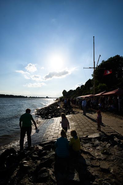 Strandperle bei Sonne an der Elbe mit Menschen im Gegenlicht Hamburg
