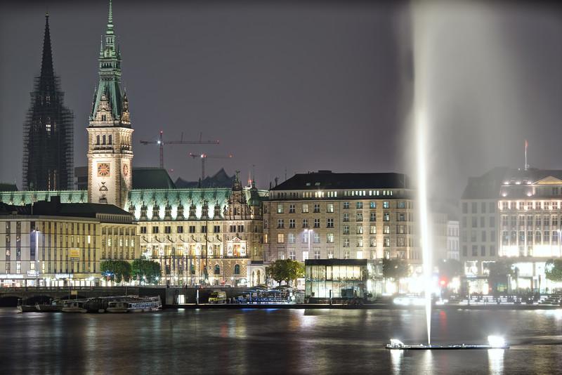 Rathaus und Binnenalster mit Wasserfontäne bei Nacht