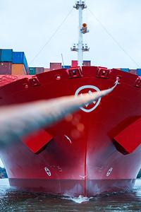 Containerschiff im Hamburger Hafen an der Schleppleine vom Schlepper