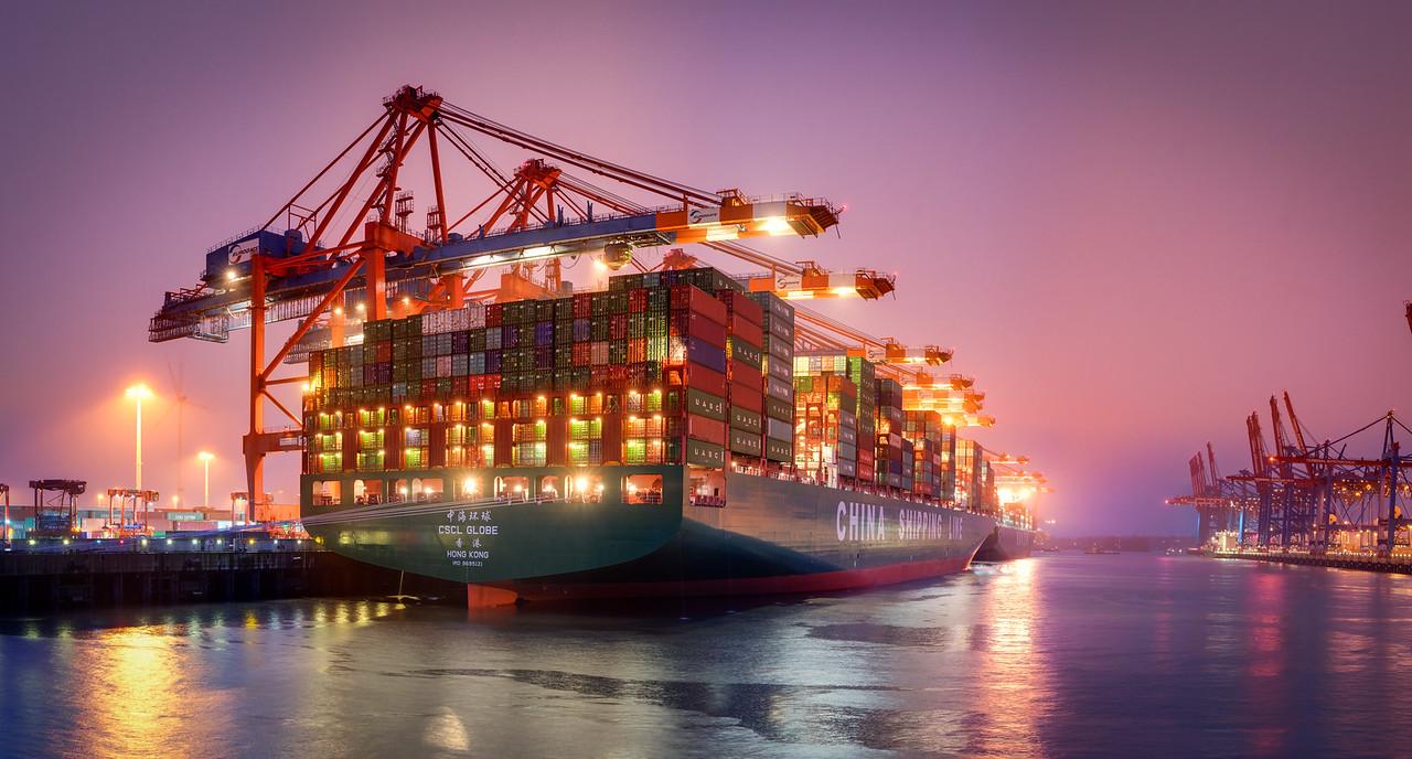 Hamburg Waltershofer Hafen mit Containerschiff bei Nacht bunt angeleuchtet