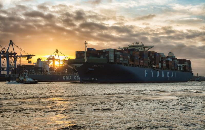 Containerschiff Hyundai beim Einlaufen in den Hamburger Hafen am Abend mit Schlepper Peter