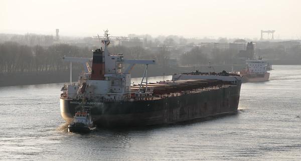Massengutfrachter verlässt Hamburg auf der Elbe mit Schlepper