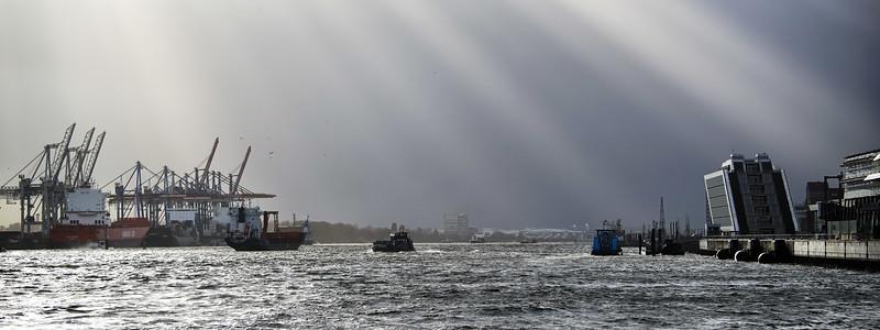 Elbe mit Athabaskakai und Dockland bei Sonnenschein vor dunklem Himmel