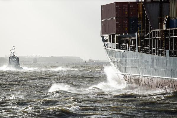 Viel Wind in Hamburg auf der Elbe Containerschiff und Schlepper