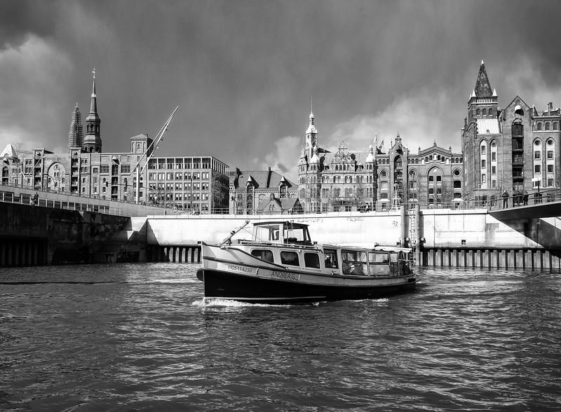 Magdeburger Hafen in Hamburg mit Barkasse und Speicherstadt im Hintergrund in Schwarzweiß
