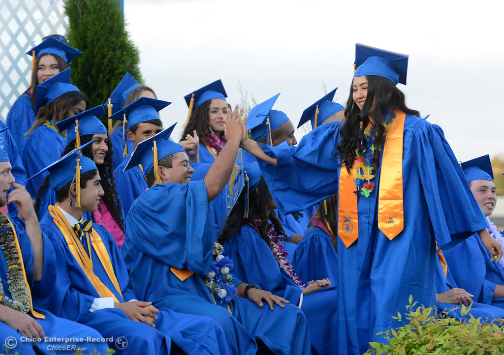 . Liliana Mata, right, gets a high-five from Cristobal Llamas after she helps announce the class gift as Hamilton High seniors graduate Friday, June 9, 2017, in Hamilton City, California. (Dan Reidel -- Enterprise-Record)