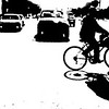 Biker on way to get gas, cars on street