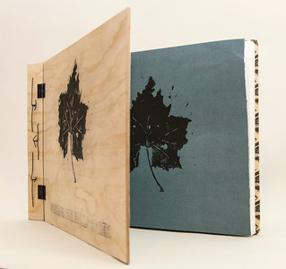 Wooden front cover with block printed image, also repeated on first page of book