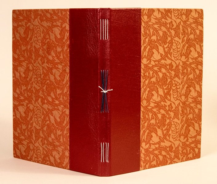 Opened cover of book showing spline stitching with leather and paper cover.