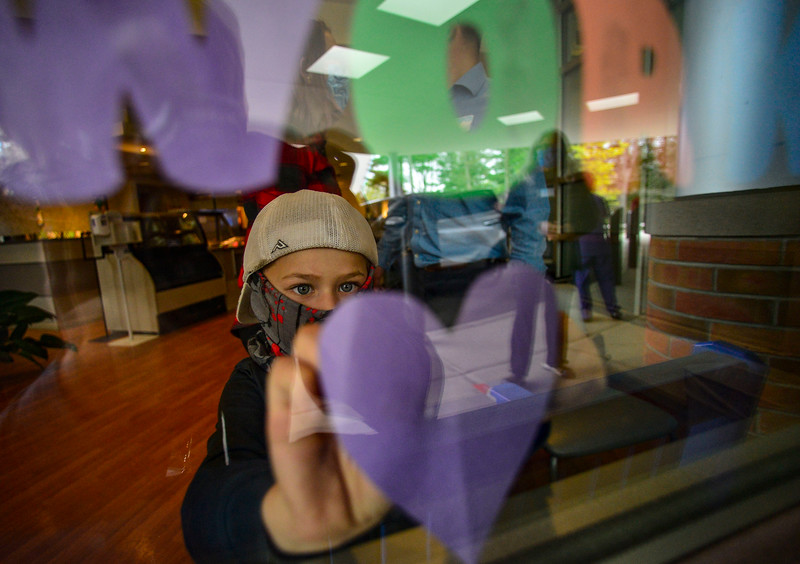 KRISTOPHER RADDER — BRATTLEBORO REFORMER<br /> Grayson Hodgman, 6, a kindergartner at Hinsdale Elementary School, in Hinsdale, N.H., puts hearts up on the window at Brattleboro Memorial Hospital, in Brattleboro, Vt., as a nurse watches through the window on Friday, May 8, 2020. The hearts were part of a class project that required the students to hang up hearts in a visible area for essential workers to see.