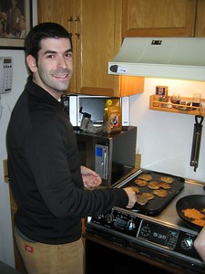 David prepares fresh latkes.  On the left are traditional, and on the right are sweet potato with carrot and pineapple.