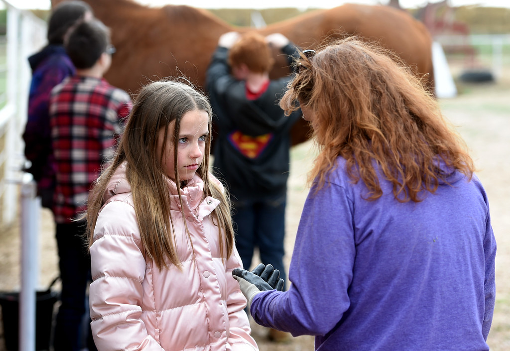 . Megan Harris, left, has a heart to heart with Kim Swaney on Tuesday. The organization, Happiness Through Horses, helps kids gain confidence by working with horses at Rockin Moon Ranch near Ft. Lupton.  Cliff Grassmick / Staff Photographer/ March 27, 2018