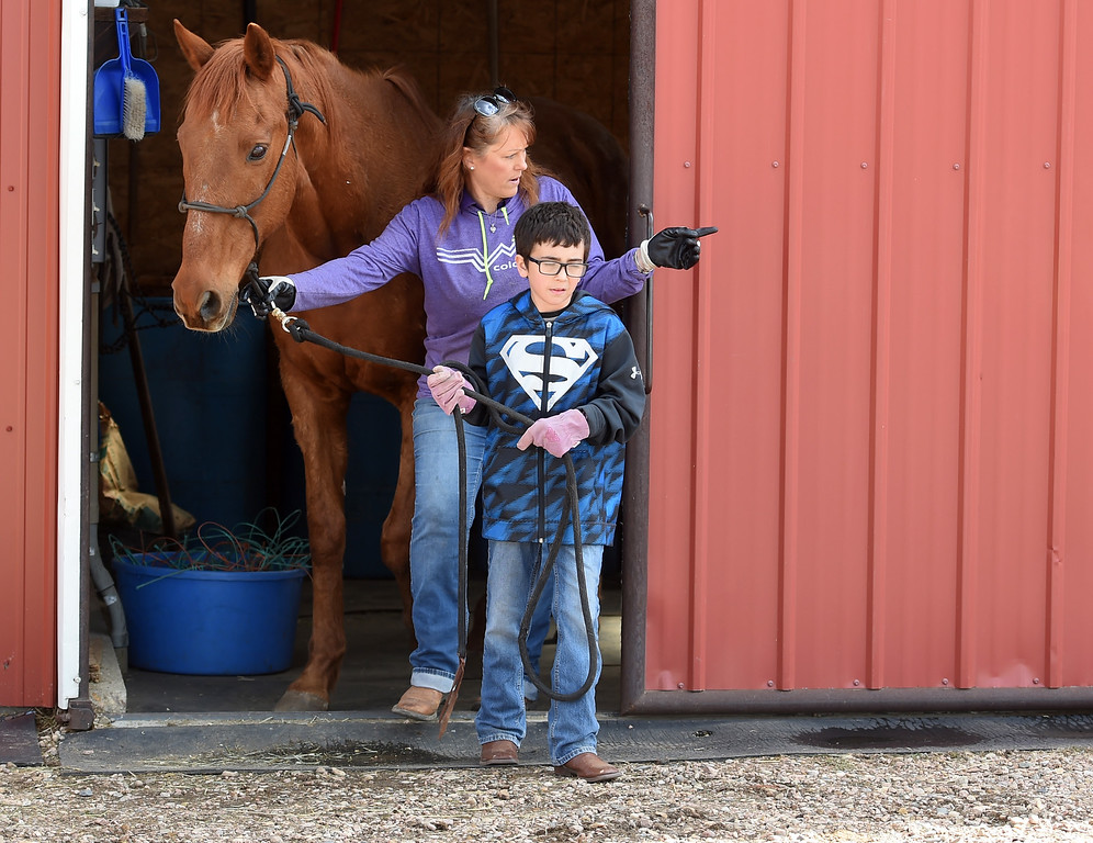 . Adam Gould, and Kim Swaney, take out one of the horses for grooming. The organization, Happiness Through Horses, helps kids gain confidence by working with horses at Rockin Moon Ranch near Ft. Lupton.  Cliff Grassmick / Staff Photographer/ March 27, 2018