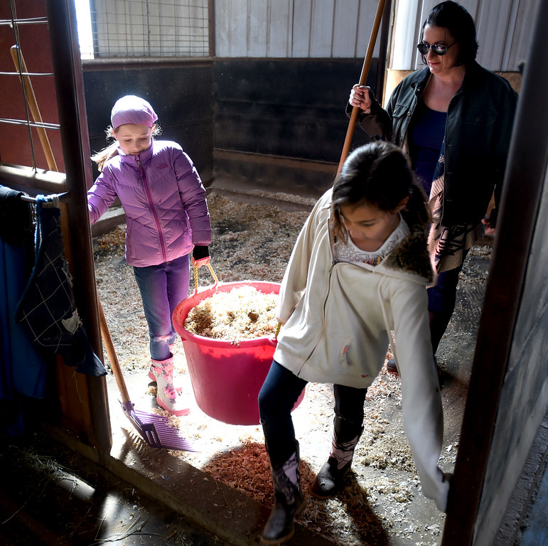 . Sam Larson, left, and Lexee Ingram, take out a bucket of droppings while Crystal Ingram supervises. The organization, Happiness Through Horses, helps kids gain confidence by working with horses at Rockin Moon Ranch near Ft. Lupton.  Cliff Grassmick / Staff Photographer/ March 27, 2018