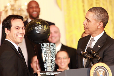 Miami Heat coach, Erik Spoelstra holding the back to back trophy presented to the President.