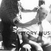 Tony Scrivanich having his hair cut by Marco Malich.  Alaska-1962