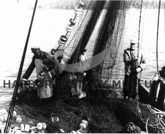 "Piling net on ""Home II"".  Howard Cox on rt.; Frank Ivanovich on left."
