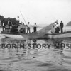 "Photographer:  Ebba Uddenburg<br /> ""Eagle"" owned by Peter Skansie<br /> One of first boats to be powered by gasoline engine about 1910.<br /> Boat leaving Gig Harbor bay.<br /> Members of Peter Skansie family on board."