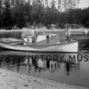 "Date:  1909<br /> Source:  Unknown<br /> Joseph Skansie's boat ""Standard"" in Gig Harbor bay.  Peter Skansie, Andrew and Vincent.  Turntable on stern used to maneuver stacked net. Rollers on turntable would help crew pull in nets by hand. Floatingcabin in the background."