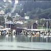Gig Harbor Marina and west side of Gig Harbor in  1982.  The big Gig Harbor Marina sheds are at center.  The shed on the right was remodeled into business retail space in 1995.  Skansie Brothers Park with the netshed is at right.  Pioneer Way goes up the hill.  The gray Tarabochia Apartments are at the right.  Rose Tarabochia brought the buildings into Gig Harbor on barges, and then transported them up the hill.  Source Chamber of Commerce