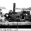"Source: Kay Weaver<br /> Date:  <br /> August 1, 1941<br /> Firewood stacked on scow with engine, along side dock at ""Head of Bay,"" Central II moored along scow."