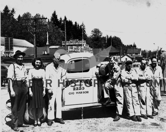 Source:  Don Edwards by Joe Hoots<br /> Photographer:  Johnson-Kemp<br /> Employees of Johnson Motor Co 1940s, N. Gig Harbor. Finholms/Far West market in background with Frozen Food Lockersllll.  Post office, Grand Stand, former McKee's Meat Market and T.C. Sweeney residence in background.  <br /> Employees:  L-R:  Ralph Johnson, Wilma Rasmussen Grissom, Mel Grissom, Don Sehmel, Pres Allen, Don Edwards (family former owners of garage at this site), Albin Olsen.