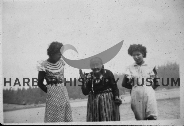 Mrs. Annie Squally with grand daughters near the Berg Landing dock.  1930s.  Claimed to be over 100 years old.  They lived on reservation located just inside the bay on the Pt. Fosdick side (east side).  From Mrs. Charles Kirby.