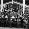 Source:  Beverly Dahl     <br /> Date:  Early 1900's     <br /> G.A.R. - men and women - south Tacoma.  Note ribbons on women - probably women's organization. <br /> Only about 4 men in picture; also carrying umbrella's - they part of the costume?