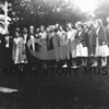 Source:  Lola (Spodoni) Elford     <br /> Date:  Unknown      <br /> Peninsula singers - directing singing group.