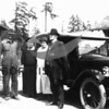 Source:  Allan Nichols     <br /> Date:  Unknown     <br /> Elwin Nichols (overalls) and wife on left (?)  Unknown couple standing beside car.