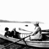 Mary Goodman manning oars of rowboat with two little boys.