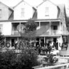 Axel Uddenberg home and grocery store.<br /> Store customers on lower porch.  <br /> team of horses hitched to delivery wagon.<br /> Road in front of house along water's edge leading to loading dock.