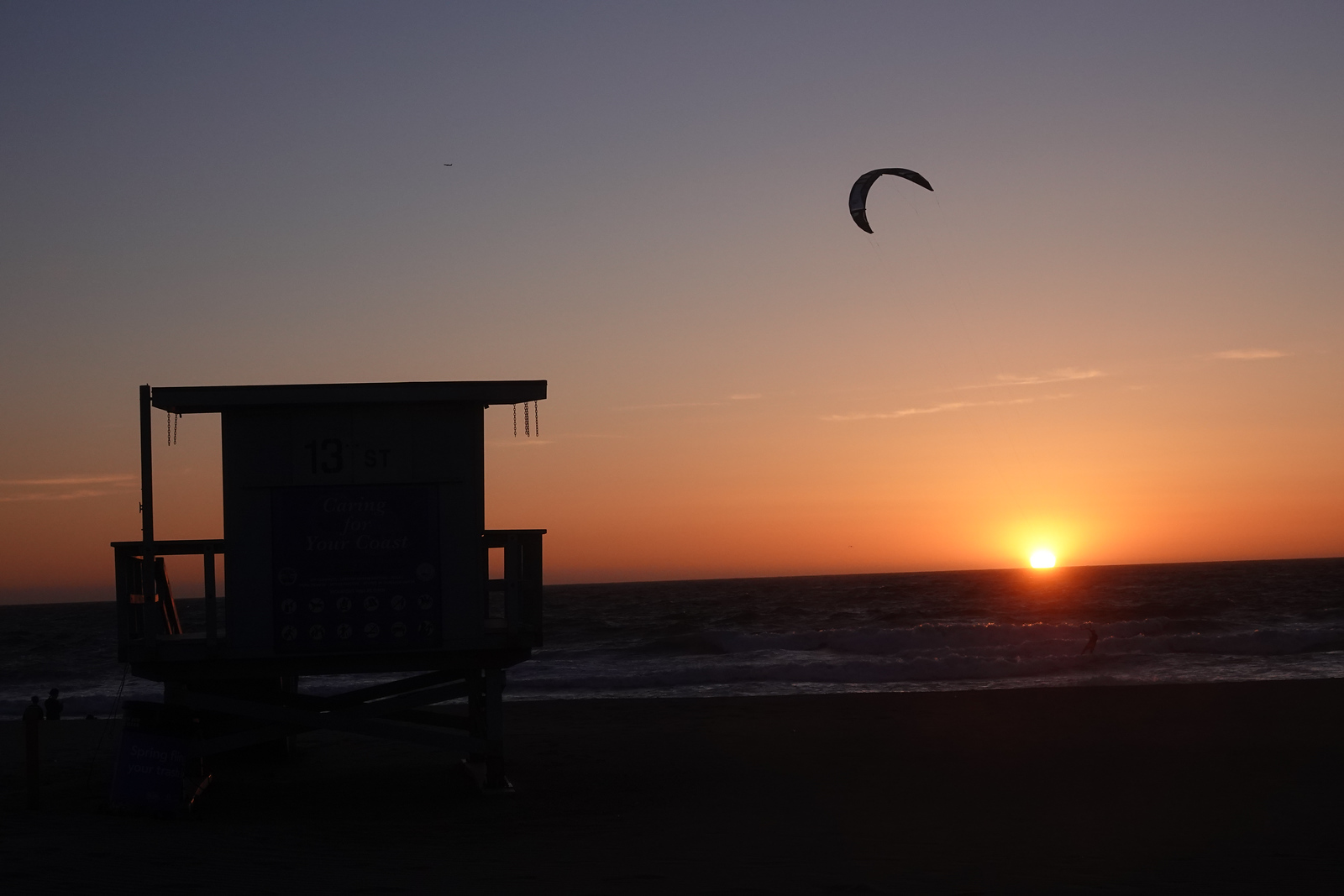 A kite flies over a lifeguard station at sunset in Hermosa Beach