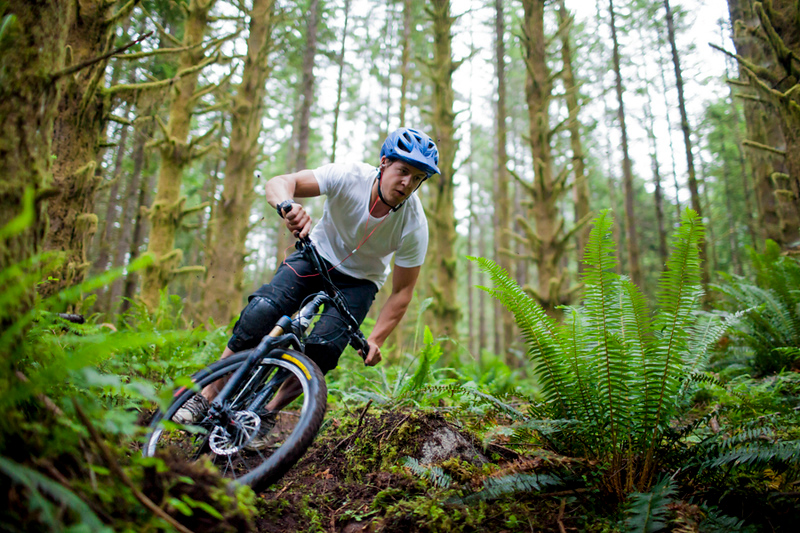 Mountain biking through a lush forest in Vancouver, British Columbia, Canada.