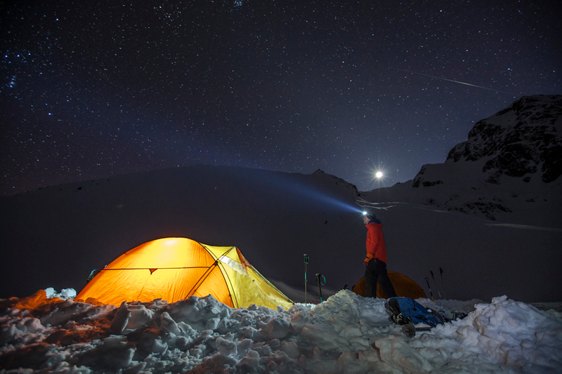 A 30-second exposure shows a climber standing beside his lit up tent under a starry night sky.