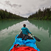 A woman paddles her canoe while rain jackets lay out to dry during a multi-day canoe trip