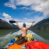 A young holds her paddle above her head while canoeing across Lanezi Lake in Bowron Lake Provincial Park.