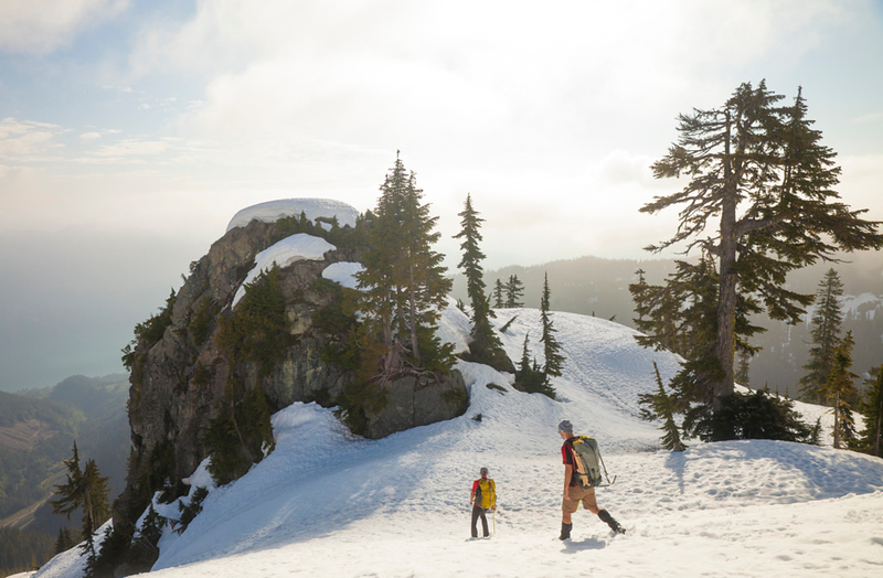 Two climbers descend a snowfield after a trip into the mountains.