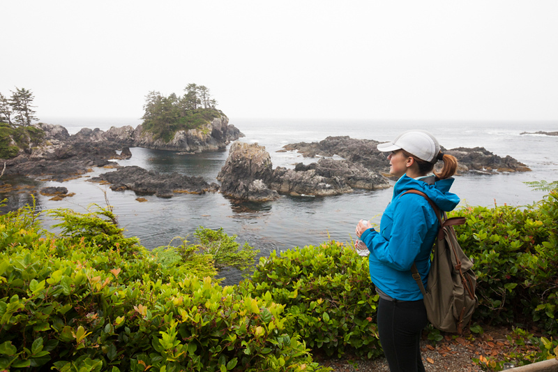 A young athletic woman stops at a viewpoint along the Wild Pacific Trail, Vancouver Island, British Columbia.