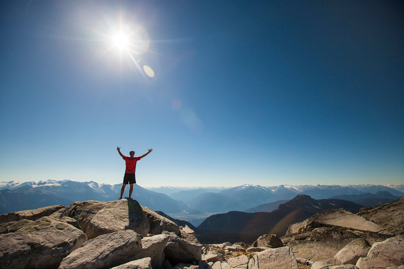 A hiker celebrates after reaching the summit of Cassiope Peak near Pemberton, British Columbia, Canada.