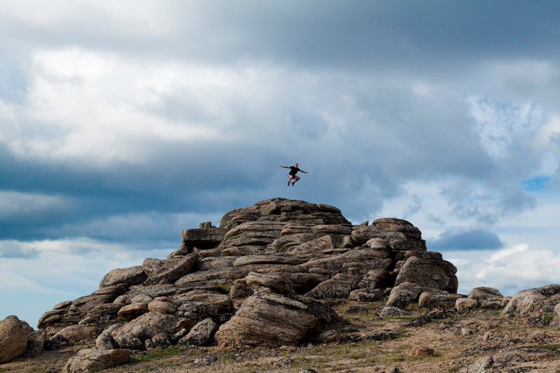A backpcaker jumps into the air off a rocky formation in Cliff City, a area with unique geology in Cathedral Lakes Provincial Park, British Columbia, Canada.
