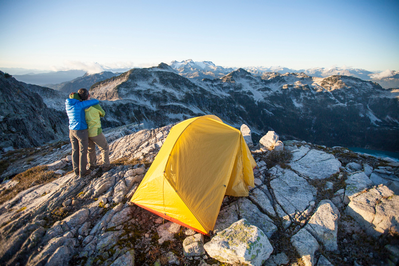 A couple admire the mountain view while camping on a rocky mountain ridge.