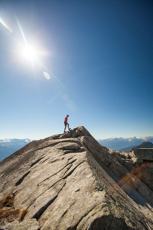 A hiker walks along a rocky ridge while on the summit of Cassiope Peak near Pemberton, British Columbia, Canada.