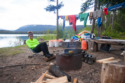 A woman relaxes by a fire while camping at Unna Lake in Bowron Lake Provincial Park.
