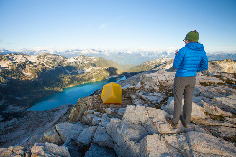 A young female backpacker eats an energy bar for dinner while looking down towards Pinecone Lake from Seed Peak