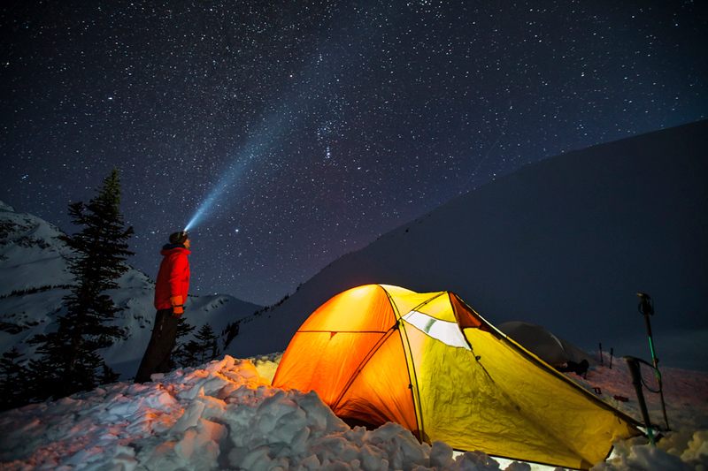 A single 30-second exposure shows a climber standing beside his lit up tent under a starry night sky near Whistler, British Columbia, Canada.