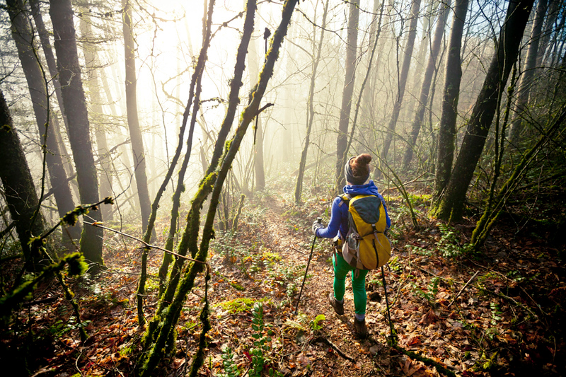 A young active backpacker hiking through a dense foggy forest.