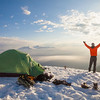 A camper watches the sunrise from his campsite on a snow covered mountain.
